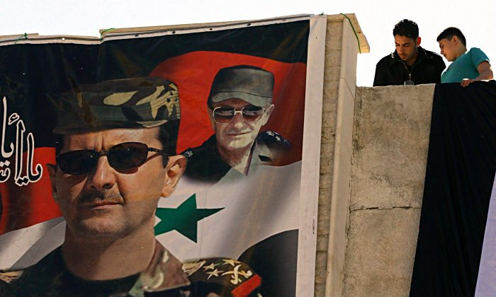 A poster of Syrian President Bashar al-Assad (L) and his late father and predecessor Hafez al-Assad in Damascus on May 1. (Louai Beshara/AFP/Getty Images)