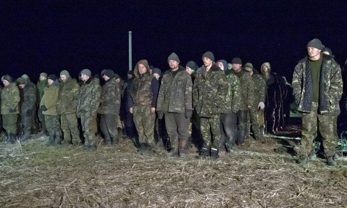 Ukrainian prisoners of war wait in line before a prisoner exchange in Russia-backed separatist controlled territory, near the village of Zholobok, some 20 kilometers (12 miles) west of Luhansk, Ukraine. (AP Photo/Vadim Ghirda)