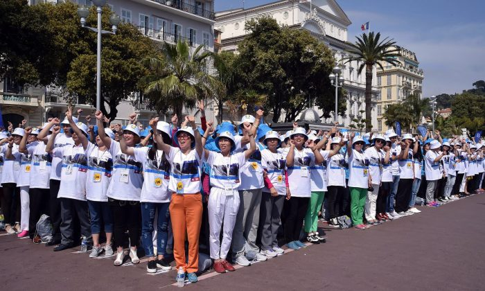 Employees of the Tiens Group at a parade in France on May 8. A number of Chinese firms have rewarded employees with identical package tours. (AP Photo/Lionel Cironneau, File)