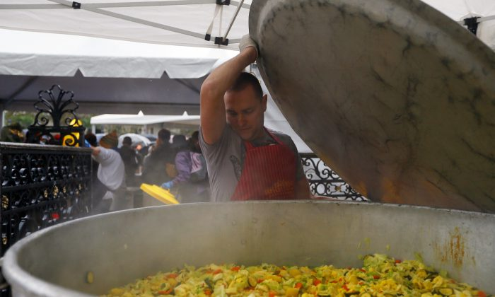 A man cooks vegetables during an event to raise awareness of the food waste on October 13, 2012 at the Place de l'Hotel de Ville in Paris.  (Kenzo Tribouillard/AFP/GettyImages)