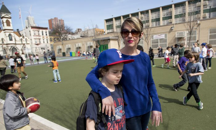 Kristen Couse walks with her son, Wile, on the playground at Public School 261, Thursday, April 16, 2015, in the Brooklyn borough of New York. (AP Photos/Mark Lennihan)