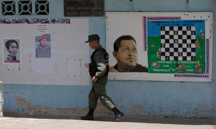 A Bolivarian National Guards officer walks near images of the late Venezuelan President Hugo Chavez and Independence hero Simon Bolivar, left, at a poll station in Caracas, Venezuela, Sunday, May 17, 2015. (AP Photo/Fernando Llano)