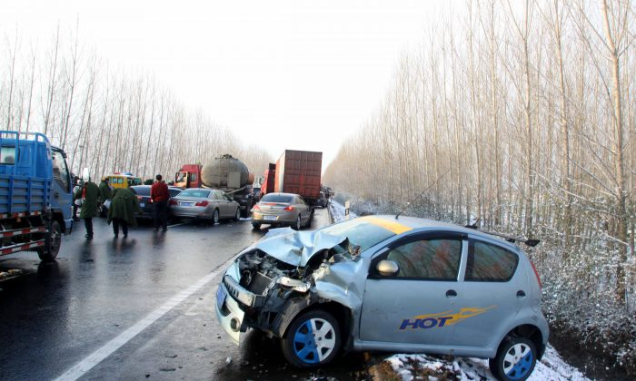 People check their damaged cars beside the pile up of over 100 vehicles after a crash along a highway in Weifang, east China's Shandong province on December 8, 2011 (STR/AFP/Getty Images)