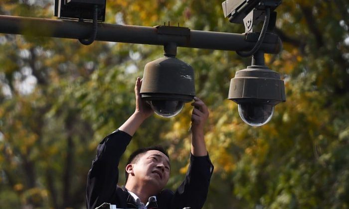 A worker adjusts security cameras on the edge of Tiananmen Square in Beijing on September 30, 2014. (GREG BAKER/AFP/Getty Images)