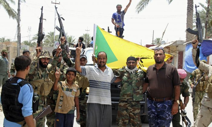 Local residents and Sunni tribal fighters welcome newly-arriving Iraqi Shiite Hezbollah Brigade militiamen, brandishing their flag, who are joining the fight against Islamic State group militants in Khalidiya, 100 kilometers (60 miles) west of Baghdad, Iraq. (AP)