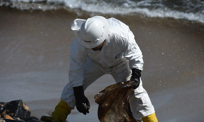 A worker cleans oil from the rocks and beach at Refugio State Beach in Goleta, Calif., near Santa Barbara and northwest of Los Angeles on May 22. (Mark Ralston/AFP/Getty Images)