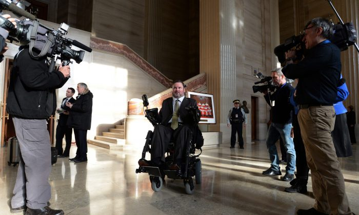 """Conservative MP Steven Fletcher makes his way through the foyer of The Supreme Court of Canada in Ottawa on Friday morning, Feb. 6, 2015. The Supreme Court unanimously struck down the ban on providing a doctor-assisted death to mentally competent but suffering and """"irremediable"""" patients. (The Canadian Press/Sean Kilpatrick)"""