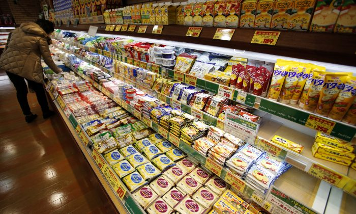 In this Tuesday, Dec. 9, 2014 photo, a shopper chooses dairy products as the shelf selling butter, right, is almost empty at a supermarket in Tokyo. (AP Photo/Shizuo Kambayashi)
