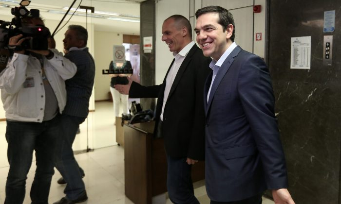 Greece's Prime Minister Alexis Tsipras, right, is welcomed by Finance Minister, Yanis Varoufakis, during his visit at the Finance Ministry in Athens Wednesday, May 27, 2015. (Costas Baltas/InTime News via AP)