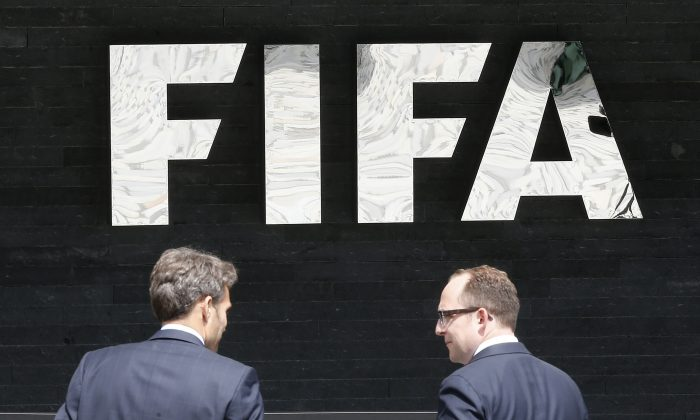 Two men talk to each other in front of the FIFA logo at the FIFA headquarters in Zurich, Switzerland, on May 27, 2015. (AP Photo/Michael Probst)