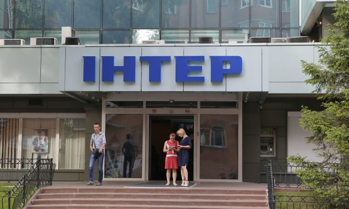 People walk out off of Inter TV channel in Kiev, Ukraine,Tuesday, May 26, 2015.  (AP/Sergei Chuzavkov)