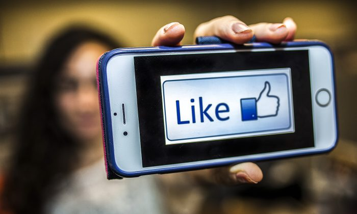 """A woman shows a picture of a """"like"""" button on her phone in New York on May 28, 2015. (Petr Svab/Epoch Times)"""