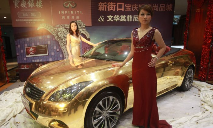 Models pose with a gold-plated Infiniti luxury sports car at a jewellery store in Nanjing, east China's Jiangsu province on March 31, 2011. (STR/AFP/Getty Images)