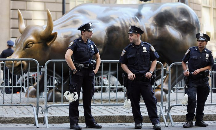 Police guard the famous bull statue during Occupy Wall Street protests in the Financial District in New York on Sept. 17, 2012. Taming the irrational exuberance of bankers is key to avoiding another crisis, argues Anjan V. Thakor. (Mario Tama/Getty Images)