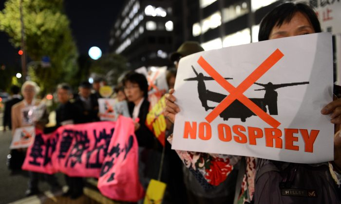 A protester displays a 'No Osprey' poster during a protest rally against U.S. military bases in Okinawa, in front of the Japanese prime minister's official residence in Tokyo on Oct. 24, 2012. Recent plans for a new base on the north of the island have intensified opposition to U.S. military bases. (TOSHIFUMI KITAMURA/AFP/Getty Images)