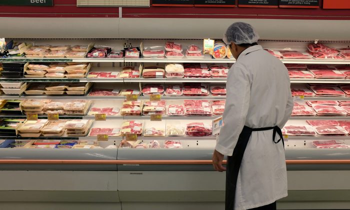 An employee checks up on meat at a grocery store in Miami on July 8, 2014. ( Joe Raedle/Getty Images)