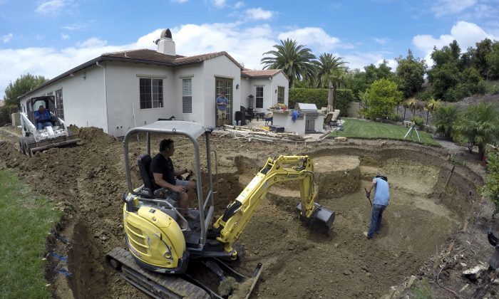 A construction crew digs a new pool behind a house in Tustin, Calif., on May 20, 2015. (AP Photo/Gillian Flaccus)