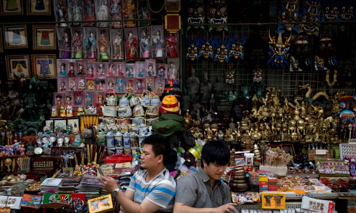 Vendors browse their smartphones as they wait for customer at their store selling Chinese made souvenirs at the Wangfujing shopping district in Beijing on May 21, 2015. (Andy Wong/AP)
