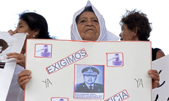 "In this file photo, women hold posters with portraits of disappeared people reading ""We demand justice now"" as former Salvadorean Minister of Defense (1983-1989), Eugenio Vides Casanova (out of frame), arrives to Monsignor Oscar Romero international airport in San Luis Talpa, 44 km south of San Salvador on April 8, 2015. (Marvin Recinos/AFP/Getty Images)"
