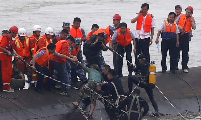 """A survivor (C-green top) is rescued by divers from the Dongfangzhixing or """"Eastern Star"""" vessel which sank in the Yangtze river in Jianli, central China's Hubei province on Tuesday."""