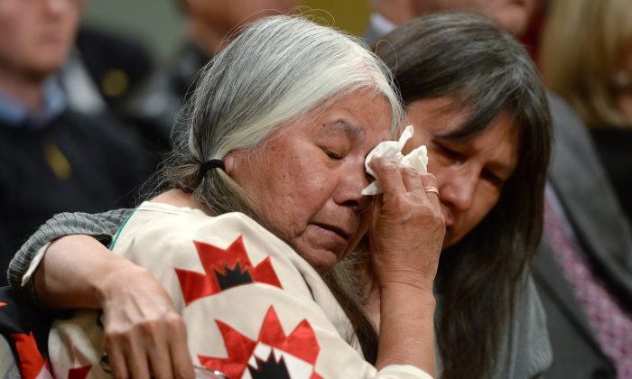 A woman is comforted in the audience during the closing ceremony of the Indian Residential Schools Truth and Reconciliation Commission, at Rideau Hall in Ottawa on Wednesday, June 3, 2015. (The Canadian Press/Sean Kilpatrick)