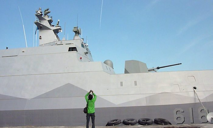 A journalist (C) takes a photo of Taiwan's first domestically-produced missile corvette, the 500-ton ship Tuo Chiang (Tuo River), during the vessel's launch ceremony at the naval port at Suao in northeastern Taiwan's Yilan county on December 23, 2014. (Benjamin Yeh/AFP/Getty Images)