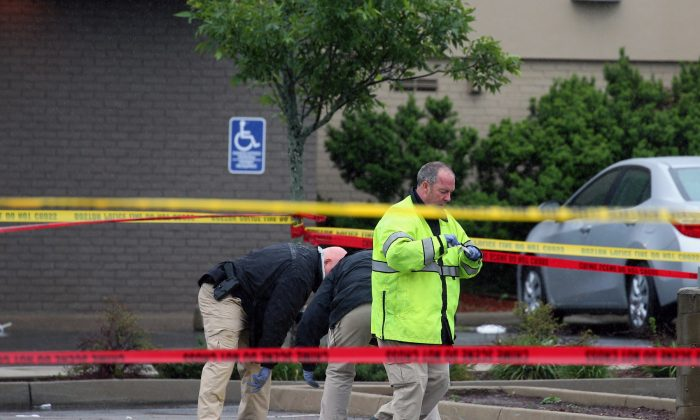 Boston police officers and detectives investigate the scene of a shooting Tuesday, June 2, 2015, in Roslindale, Mass. A man who was under 24-hour surveillance by terrorism investigators was shot and killed after he lunged with a knife at a police officer and an FBI agent outside a pharmacy, authorities said. (Mark Garfinkel/The Boston Herald via AP)
