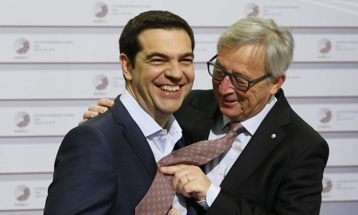 FILE - In this Friday, May 22, 2015 file photo, European Commission President Jean-Claude Juncker, right, pushes his tie up against the shirt of Greek Prime Minister Alexis Tsipras during a recent meeting in Riga, Latvia. (AP Photo/Mindaugas Kulbis, File)