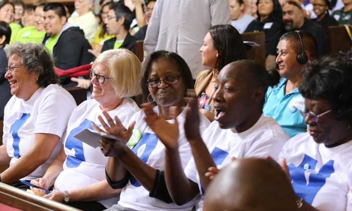 Supporters applaud during the minimum wage increase vote as the Los Angeles City Council votes to raise the minimum wage in the city to $15 an hour by 2020, making it the largest city in the nation to do so, in Los Angeles Tuesday, May 19, 2015. (AP Photo/Damian Dovarganes )
