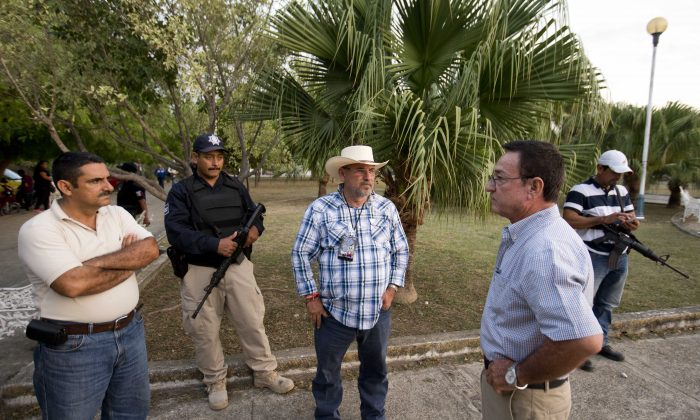 In this May 21, 2015 photo, congressional candidate, former self-defense group leader Hipolito Mora, center, waits to start a campaign meeting with residents in Coahuayana, Michoacan state, Mexico. (AP Photo/Eduardo Verdugo)