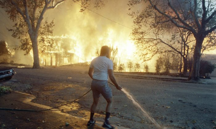 In this Sunday, Oct. 20, 1991, photo, Berkeley resident Jim Beatty stands with a garden hose as homes burn out of control in the Berkeley and Oakland hills area on in Berkeley, Calif. (AP Photo/Kevin Rice, File)