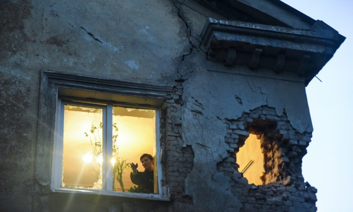 People observe damage in their flat after shelling between Russia-backed separatists and Ukrainian government troops in Donetsk, Eastern Ukraine Monday, June 1, 2015.  (AP Photo/Mstyslav Chernov)
