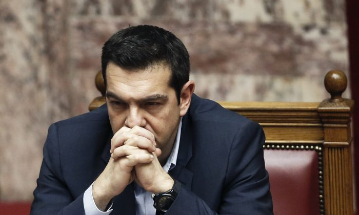 Greece's Prime Minister Alexis Tsipras, gestures during a parliament session before the conference vote in Athens, on Tuesday, Feb. 10, 2015. (AP Photo/Petros Giannakouris)