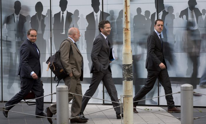 Dutch Finance Minister Jeroen Dijsselbloem, center right, walks with officials as he arrives for a meeting at EU headquarters in Brussels on Wednesday, June 3, 2015. Dijsselbloem is Brussels on Wednesday joining discussions regarding the Greek bailout. (AP Photo/Virginia Mayo)