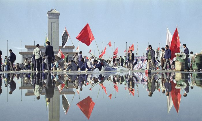 Morning activity in Beijing's Tiananmen Square is reflected in the wet pavement, May 24,1989, following a downpour the night before. In the background are the Martyrs monument and beyond that, Mao's mausoleum. (AP Photo/Mark Avery)