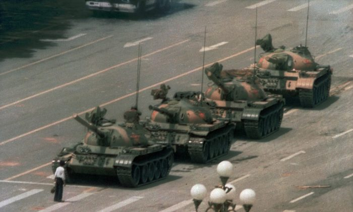 """A Chinese man, now known as """"Tank Man,"""" stands alone to block a line of tanks heading east on Beijing's Avenue of Eternal Peace during the Tiananmen Square Massacre, on June 5, 1989. (Jeff Widener/AP Photo)"""