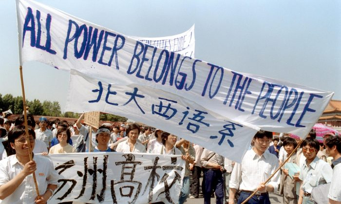 A 25 May 1989 file photo shows students waving banners as they march in Beijing streets near Tiananmen Square during a rally to support the pro-democracy protest against the Chinese government. (Catherine Henriette/AFP/Getty Images)