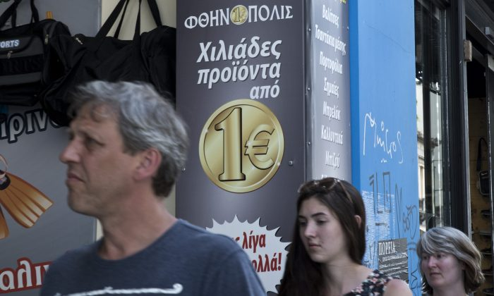 "Tourist walks past a discount shop which reads in Greek ""thousand of products from one Euro"" on Thursday, June 4, 2015.  (AP Photo/Petros Giannakouris)"