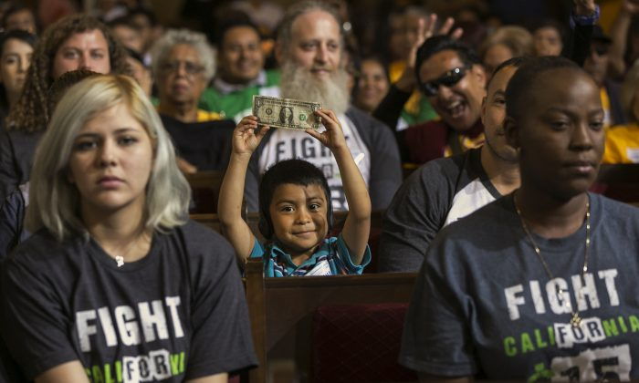 David Lazo, 5, center, with his father Francisco, right, raises a dollar bill as workers await the Los Angeles City Council's vote to raise the minimum wage in the city to $15 an hour by 2020 in Los Angeles Wednesday, June 3, 2015. (AP Photo/Damian Dovarganes)