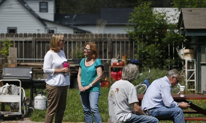 Family members of a slain man, whose name is yet to be officially released, who was shot and killed the night before, stand in the yard of the family home while police performed a search inside, in Loveland, Colo., Thursday, June 4, 2015. (AP Photo/Brennan Linsley)