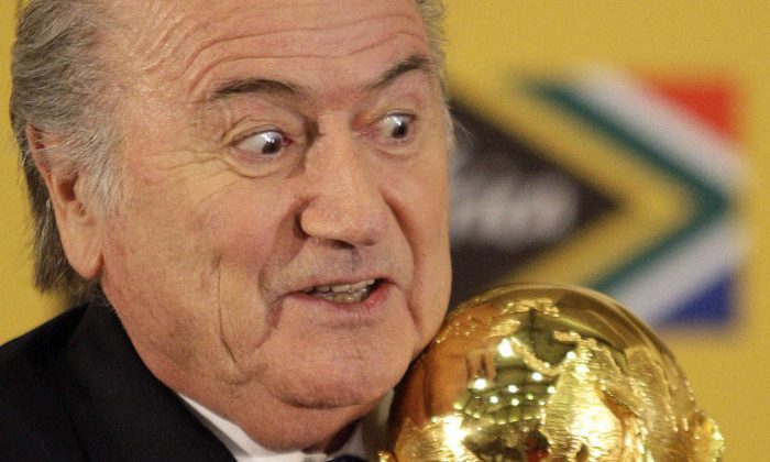 In this Sunday June 6, 2010 file photo FIFA President Joseph Blatter holds the trophy after receiving it back from South African President Jacob Zuma during a media briefing on the 2010 Soccer World Cup in Pretoria, South Africa. (AP Photo/Themba Hadebe,)