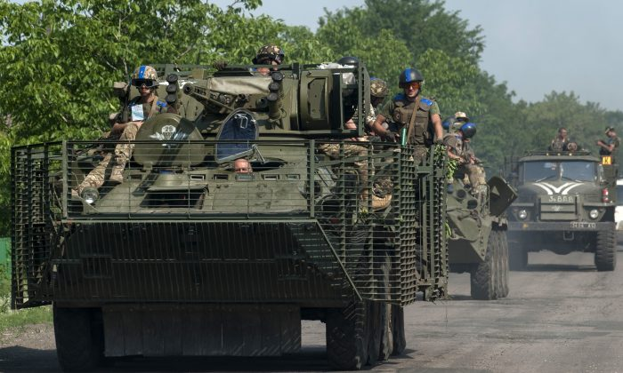 Ukrainian soldiers from the 25th airborne brigade ride on an APC on the outskirts of Marinka, Donetsk region, eastern Ukraine, Thursday, June 4, 2015. (AP Photo/Evgeniy Maloletka)