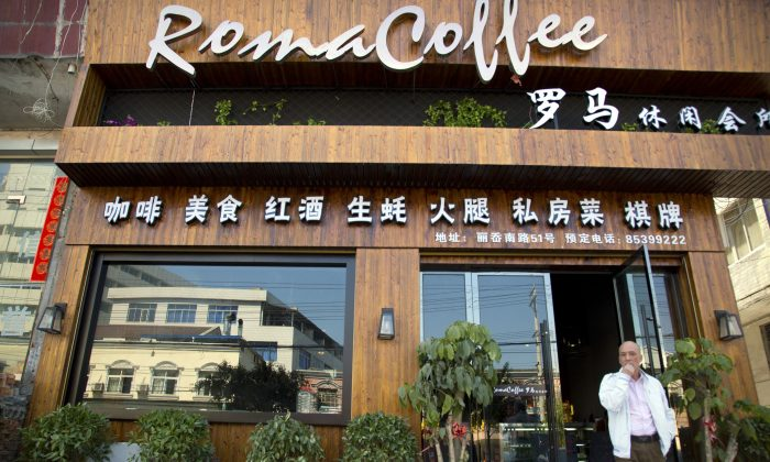 A man walks out of the Roma Coffee coffeehouse in Ao'li village in eastern China's Zhejiang Province on April 14, 2015. (AP Photo/Mark Schiefelbein)