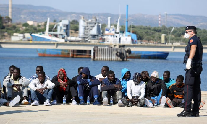 Migrants wait to be checked after disembarking from the Italian Coast Guard vessel Peluso as they arrive in the Sicilian port town of Augusta, Italy, Wednesday, June 3, 2015. Some 406 migrants were taken to Sicily after being rescued at sea in the Sicily Channel. (AP Photo/Francesco Malavolta)