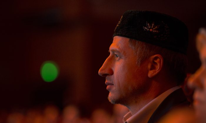 A man watches in the audience during the cultural festival celebrating the birth of the Prophet Muhammad, Mawlid an-Nabi, at the Crocus City Hall at the Moscow outskirts on Sunday, Jan. 25, 2015. A famous Muslim relic - a piece of a hair of the Prophet Muhammad, brought to Moscow from Russian Caucasus region of Dagestan was shown during the festival. (AP Photo/Pavel Golovkin)