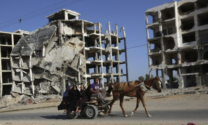 Palestinian family members ride a horse cart as they pass apartment buildings that were destroyed in the last summer's Israel-Hamas war, in the residential neighborhood of Beit Lahiya in the northern Gaza Strip, Tuesday, June 2, 2015. (AP Photo/Adel Hana)