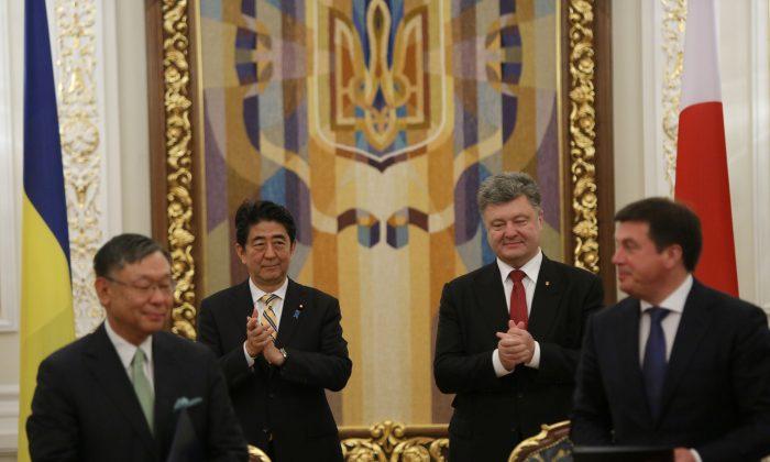 Ukrainian President Petro Poroshenko and Japan's Prime Minister Shinzo Abe, centre left, during a welcome ceremony of their meeting in Kiev, Ukraine, Saturday, June 6, 2015. (AP Photo/Sergei Chuzavkov)