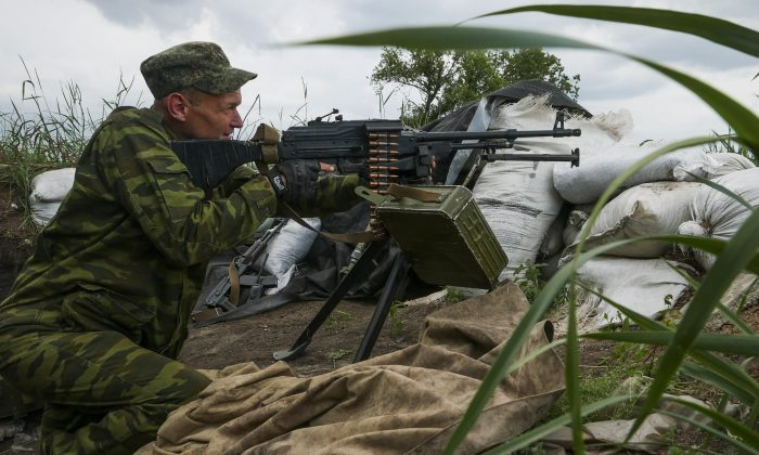 A Russia-backed rebel guards his position near the division line with the Ukrainian army near Dokuchayevsk, eastern Ukraine, on June 5, 2015. (AP Photo/Mstyslav Chernov)