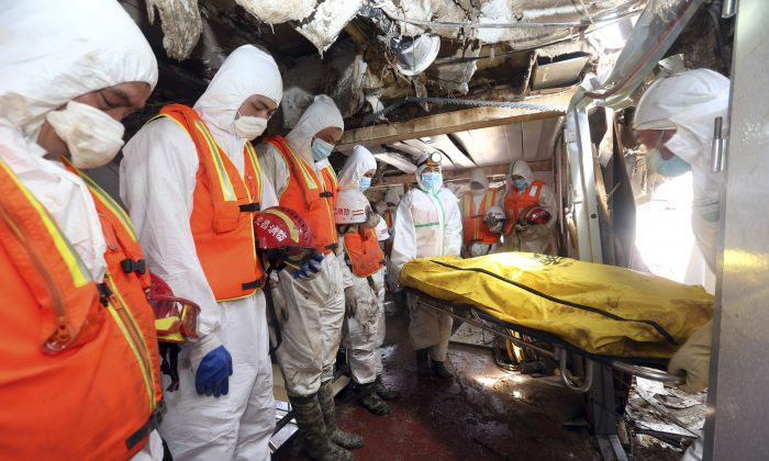Rescue workers react as a body is removed from the Eastern Star after it was righted and lifted by cranes in the Yangtze River in Jianli county in southern China's Hubei province, June 6, 2015. The death toll rose after hundreds of more bodies from the Eastern Star were found including that of a 3-year-old girl in the top deck, officials said. (Chinatopix Via AP)