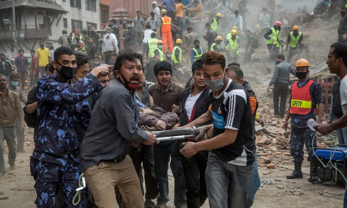 Emergency rescue workers carry a victim on a stretcher in Kathmandu, Nepal, on April 25. This earthquake is a warning to the entire Himalaya region, which is vulnerable to disasters caused by earthquakes. (Omar Havana/Getty Images)